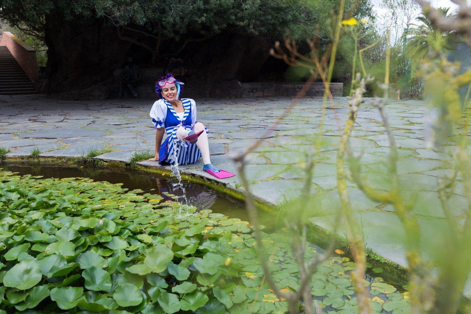 foto de una aluman del Centro de Danza Sandra Santa Cruz en el Jardín Canario con gafa, tubo, aletas y un vestuario de nadadora del siglo pasado slapicando el agua de una fuente con una de sus aletas