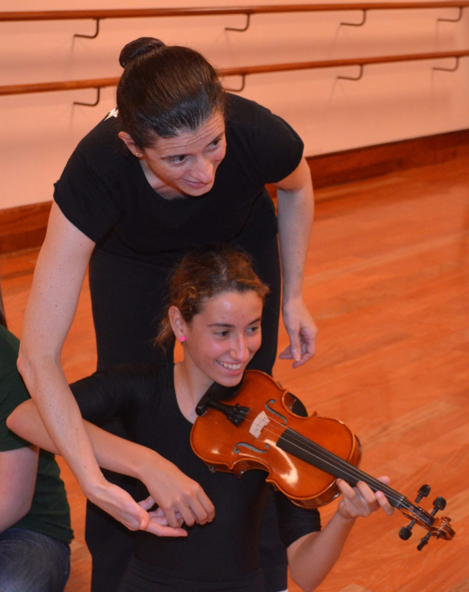 Foto de Sandra Santa Cruz explicando a una alumna cómo se toca un violín para una de sus coreografía