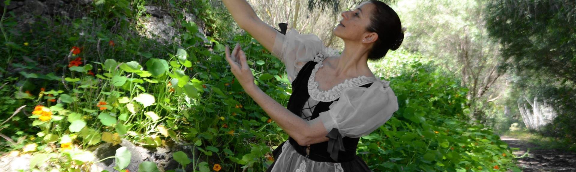 Sandra Santa Cruz baila elevando una flor en la mano en pleno campo rodeada de flores para explicar que los valores son una parte importante de la filosofía