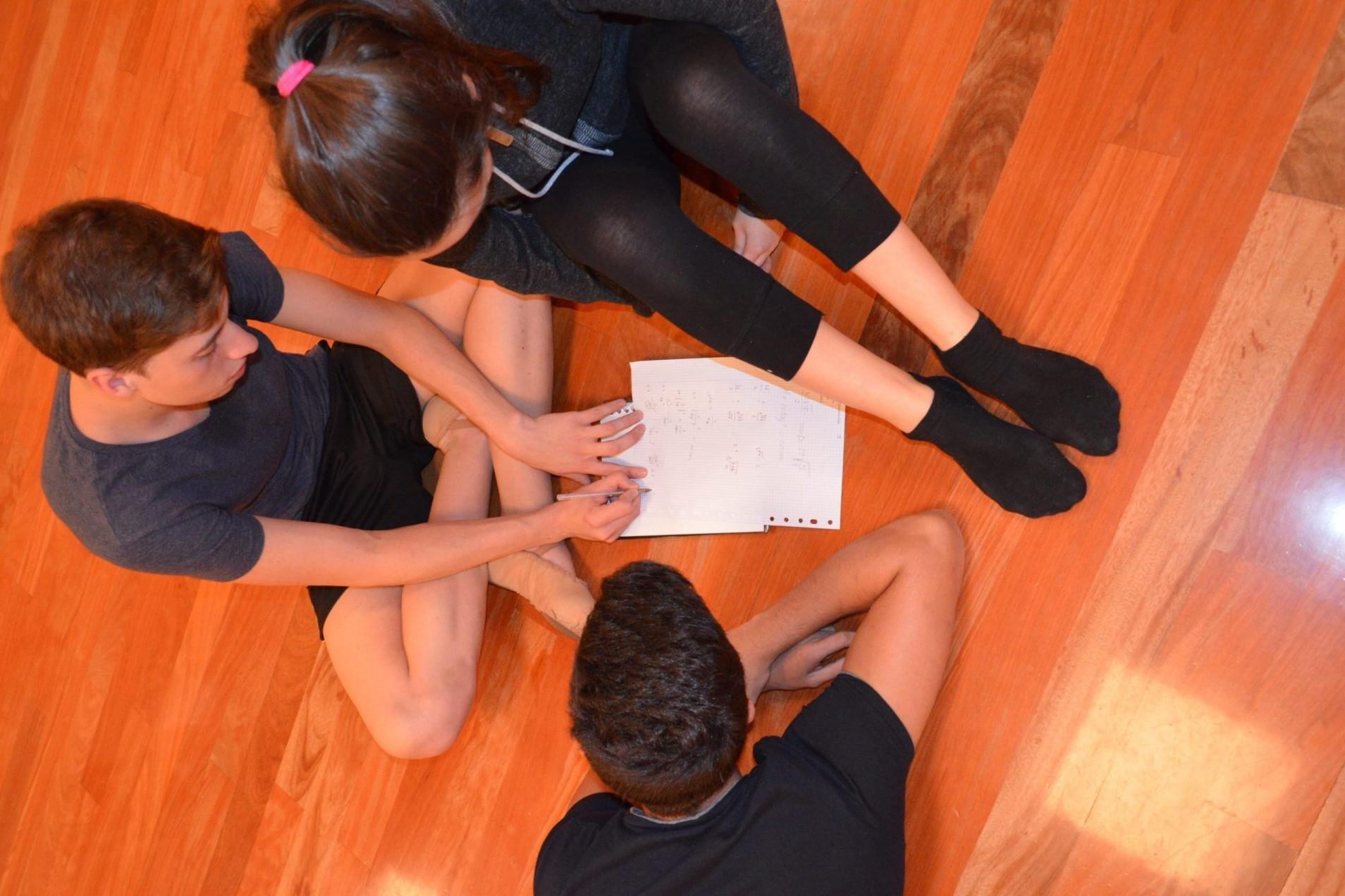 Foto de tres bailarines del Centro de Danza Sandra Santa Cruz sentados en el suelo de la sala de baile mirando unos folios que tienen delante. Aprovechan los descansos de los ensayos para estudiar. Bailar vs Estudiar, no hay que elegir, el Centro de Danza Sandra Santa Cruz fomenta una filosofía
