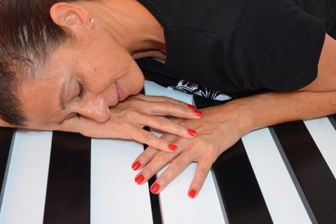 Sandra Santa Cruz_directora del Centro de Danza de su mismo nombre posa sobre las enormes teclas de un piano de grandes dimensiones