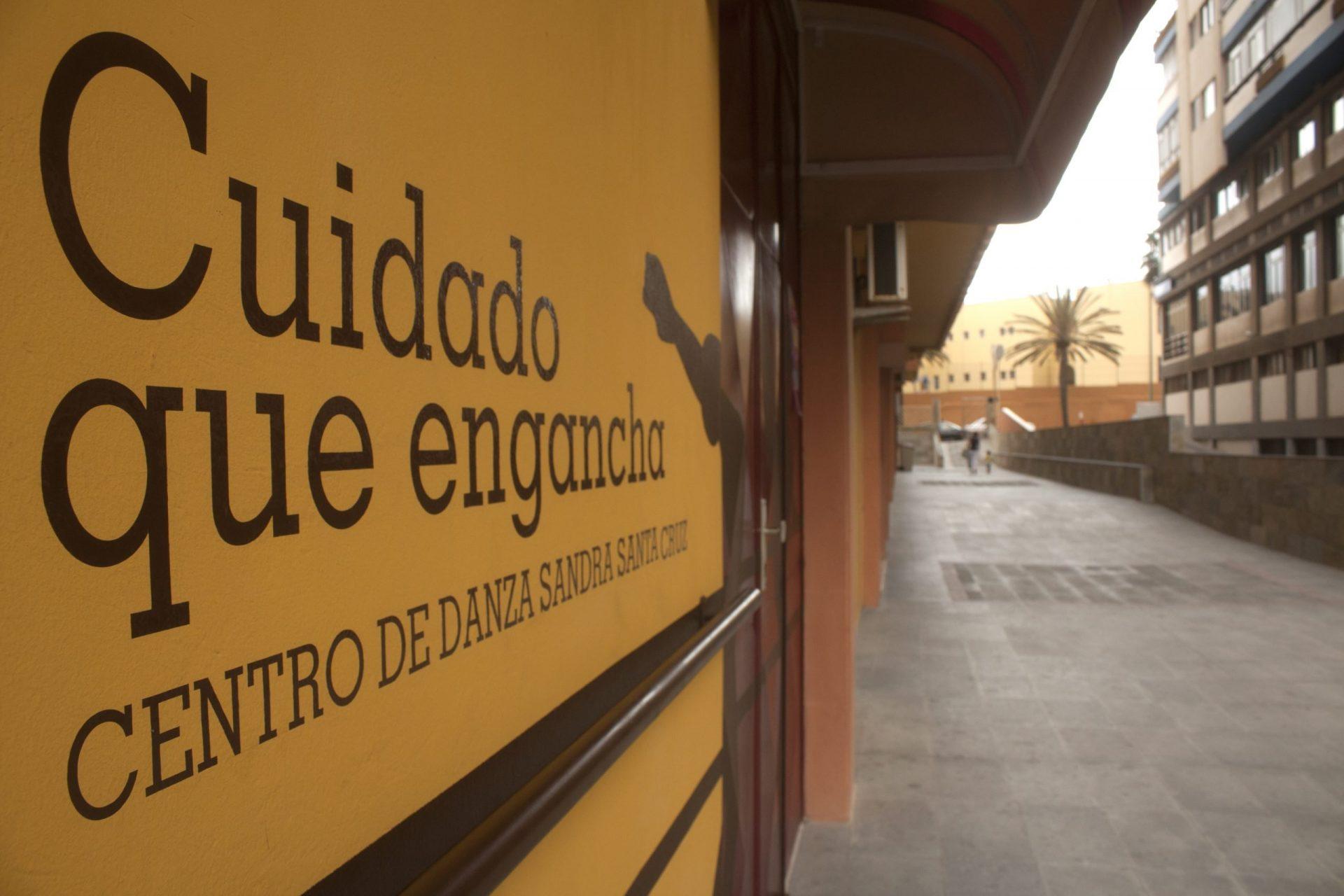 Foto de la entrada del Centro de Danza Sandra Santa Cruz donde se aprecia la barra que está puesta en su fachada y unos bailarines pintados que bailan entre la fachada y la puerta y tiene escrito debajo de Centro de Danza Sandra Santa Cruz, la frase: