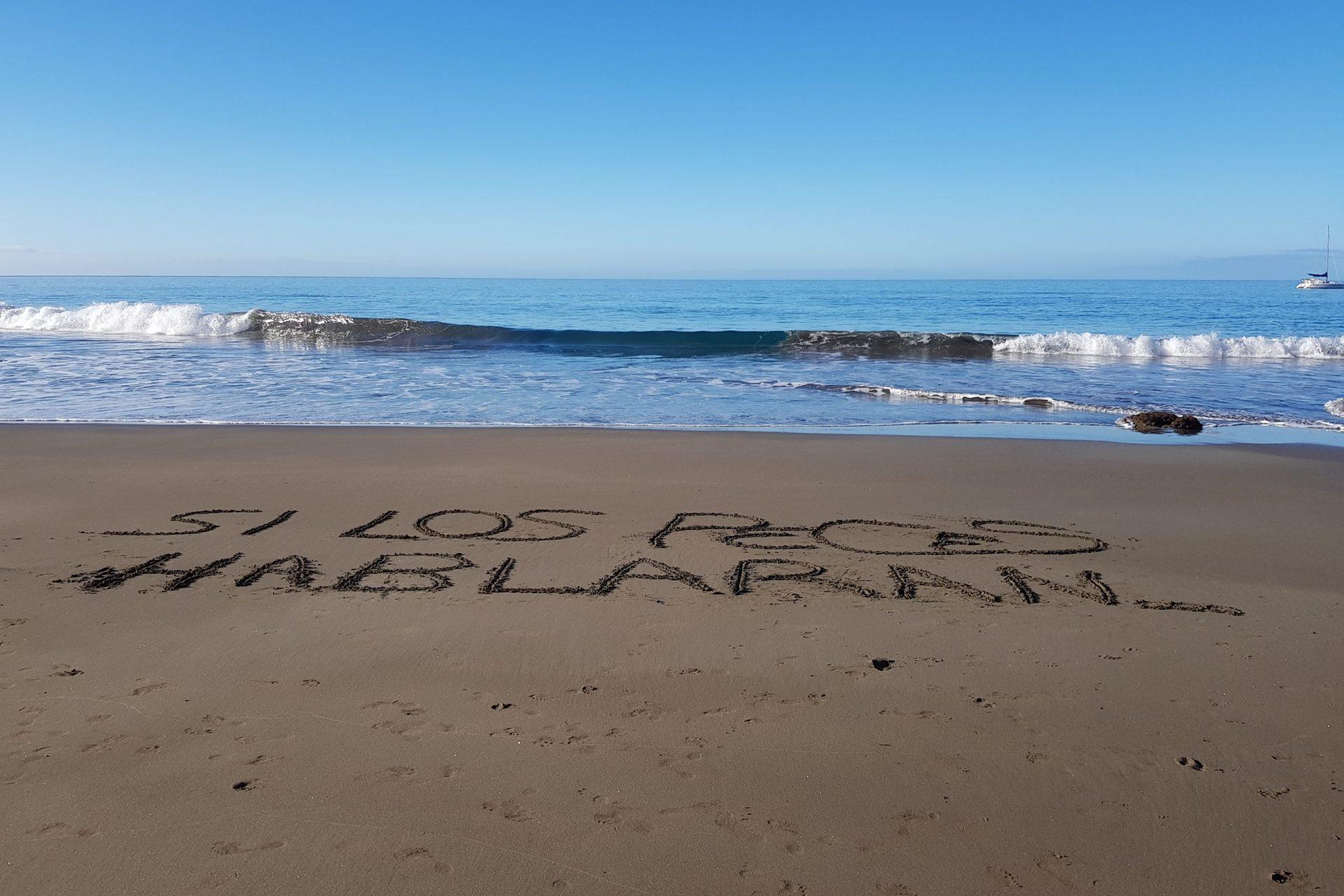 Foto en la playa de Patalavaca de una ola acercándose a la orilla donde en la arena está escrito