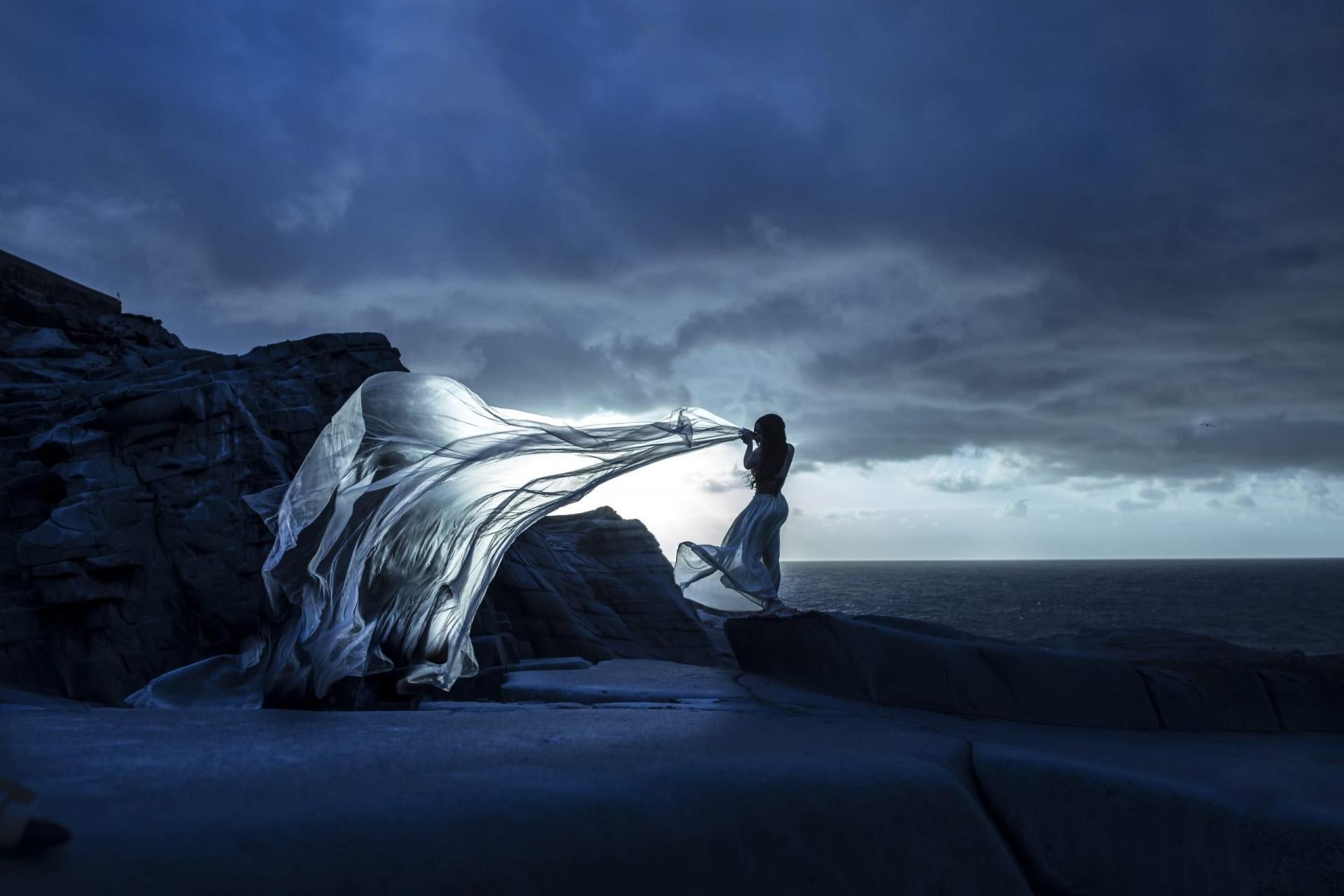 Foto de la silueta de una chica con plástico gigante en una mano que hace como una ola.