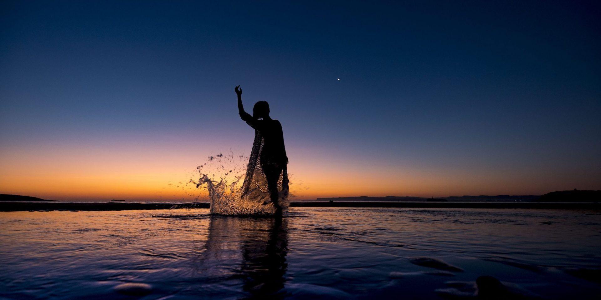 Foto de un precioso atardecer con una chica a contraluz salpicando agua en el mar. Dance Together_Centro de Danza Sandra Santa Cruz_Ethel Bartrán_DSC6079