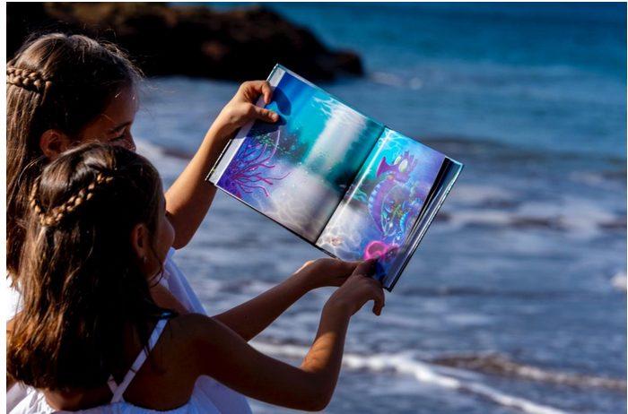 """Foto de 2 niñas en la playa leyendo el cuento de Si los peces hablaran... con el mar de fondo, y donde apararece """"Bubli"""" con su papá. Sandra Santa Cruz  conmemora así el Día Mundial de los Océanos 2021."""